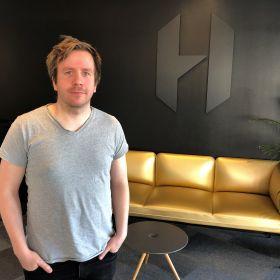Animatør Sondre Nymoen i grå T-skjorte, står foran en sort vegg med gullfarget sofa i bakgrunnen.
