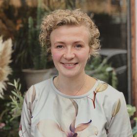 Blomsterdekoratør Kariann Lohne Hermansen står vendt mot kameraet og smiler. Rundt henne er det blomster og planter.