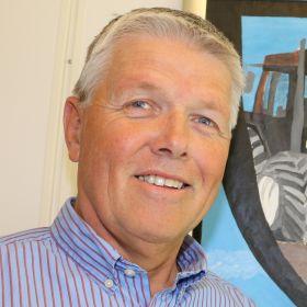 Landbruksdirektør Olav Sandlund på kontoret sitt foran et bilde av en traktor.