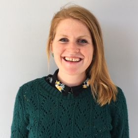 Portrett av en smilende dame med grønn genser og rødt hår
