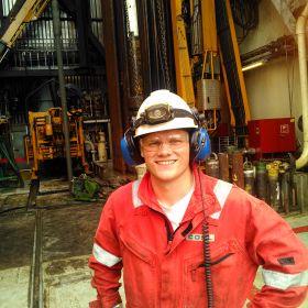 Bilder viser bore- og vedlikeholdsoperatør Knut Alfred Eriksen. Han er avbildet fra livet og opp i rød kjeledress, hvit hjelm, øreklokker, og hansker. Han står på boreplattformen der han jobber.