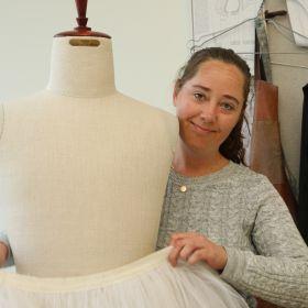 Marianne Jensen prøver et ballettkostyme på en utstillingsdukke.