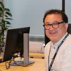 Farshad Monseni sitter ved en kontorpult, to dataskjermer i bakgrunnen.