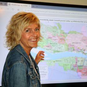 Anette Kveldsvik Desjardins står foran et kart.