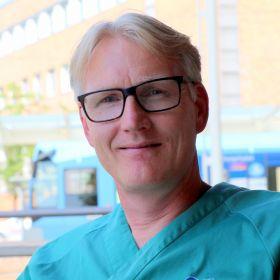 Terje Thorsvik sitter utenfor sykehuset iført blågrønt arbeidstøy. Han ser i kamera og smiler.
