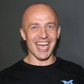 Daniel Bielen ser i kameraet og smiler stort. Han har på seg en svart genser og veggen bak ham er mørk grå.
