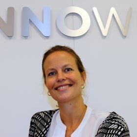 Anne Kathrine Brugård smiler og ser inn i kamera. Hun har på seg hvit bluse med en flerfarget jakke over.