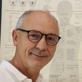 Ortoped Andreas Dietze foran en plansje av menneskekroppens muskel- og skjelettsystem.