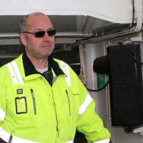 Matros Johan Dalhaug i selvlysende gul jakke og solbriller.