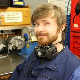 En smilende mann med skjegg i blå overtrekksdress og hørselsvern.