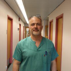 Bildet viser urolog Luca Colapaoli utenfor kontoret hans på Haugesund Sykehus. Han står i en lang gang, og er iført grønne arbeidsklær og er avbildet fra livet og opp.