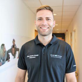 Bildet viser kiropraktor Tom Andre Hauge. Han er avbildet fra livet og opp, og er iført en svart T-skjorte. Han står i gangen på klinikken der han jobber.