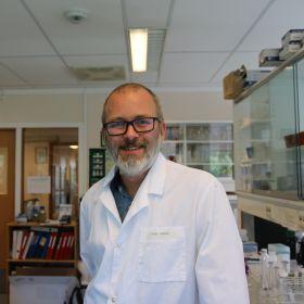 Kjemiker John A. Gjerde er avbildet på laboratoriet der han jobber. Han er avbildet fra livet og opp, og har svarte briller, skjegg og smiler mot kamera. Han er iført hvit labfrakk, og i bakgrunnen ser vi permer og arbeidsredskaper.