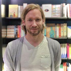 Portrettfoto av bokhandler Magne Julin Vik-Mo foran bokhylle.