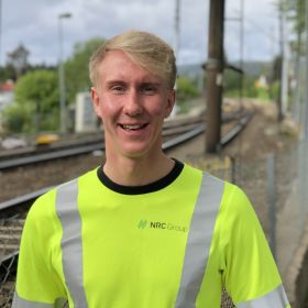 Portrett av Tom Andre Ihlen i selvlysende T-skjorte, togspor i bakgrunnen.