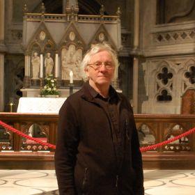 Kirketjener Ragnar Timmo Aune står foran alteret i kirken hvor han jobber.