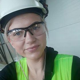 Portrettfoto av blikkenslager Elisabeth Heien. Hun har på seg hvit hjelm, beskyttelsesbriller og et grønt klesplagg og ser inn i kamera.