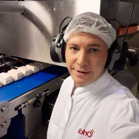 Fagarbeider industriell matproduksjon Håvard Strandos i ført hvitt arbeidstøy med Orkla-logoen på i rødt, hårnett på hodet og hørselsvern. I bakgrunnen ser vi pizzadeiger på et blått bånd. Håvard ser inn i kamera.