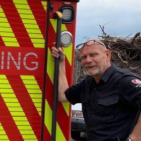 Portrettbilde av brannkonstabel Stein Inge Hollås, foran brannbilen. Gule og røde striper på baksiden av brannbilen. Stein Inge har arbeidsklær, svart t-skjorte med logo på den venstre skuldra, og briller på hodet.