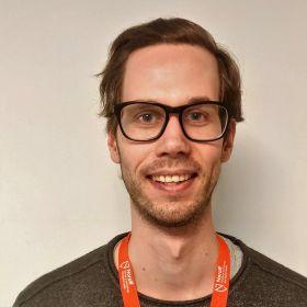 Portrett av spilldesigner Magnus Grønningen. Han står foran en nøytral bakgrunn, har på grå genser og en oransje nøkkelreim rundt halsen.