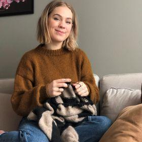 Strikkehåndverker Pia Marlene Øye Amundsen sitter i sofaen med strikketøyet på fanget.