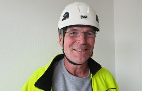 Portrett av Geir Kjærås som har på hjelm og gul arbeidsjakke.