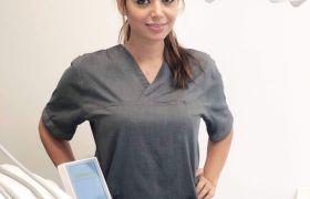 Portrettbilde av tannlege Maryam Sepahyar med grå overdel foran en tannlegestol.