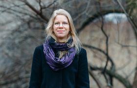 Komponist Agnes Ida Pettersen er avbildet utendørs, og vi ser noen trær uten blader i bakgrunnen. Hun er avbildet fra livet og opp, iført svart kåpe og et svart og lilla skjerf. Hun har briller og langt, blondt hår.