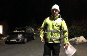 Avisbud Dominik Mysiak står ute i en mørk gate med en avis i hånden.