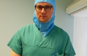 Portrett av barnekirurg Thorstein Sæter, iført tildekkende klær han bruker under operasjoner. Foto.