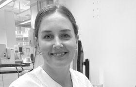 Portrettbilde av bioingeniør Ingvild Fleten Sortland, i svart-hvitt format. Hun har på seg hvitt arbeidsantrekk og smiler mens hun ser i kamera