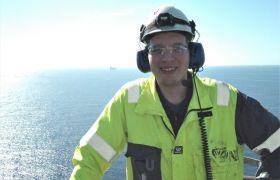 Brønnoperatør i komplettering Erlend Eivik Eliassen i arbeidsklær ute på boreriggen med havet i bakgrunnen.