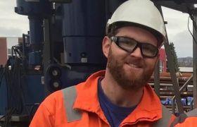 Brønnoperatør for mekaniske kabeloperasjoner Thomas Bjorland iført hjelm og orange kjeledress ute på plattform.