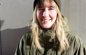 Portrett av entomolog Trude Magnussen ute med sol i ansiktet i grønn ytterjakke og lue.