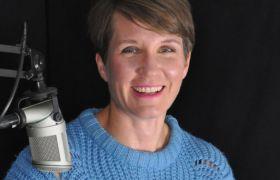 Portrettbilde av Sara Lossius i eit lydstudio, ved sida av ein mikrofon. Avbilda frå brystet og opp, med blå strikkegenser.