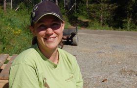 Dyrepassar Ann-Karin Steinkjer i grøn te-skjorte og caps smiler mot kamera.