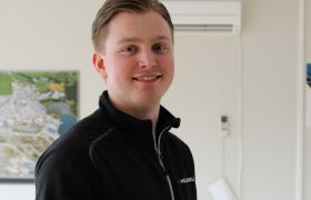 Elektriker Håkon Knudsen Kvinnsland med ledninger i hånden. Han er kledd i svarte arbeidsklær. Foto.