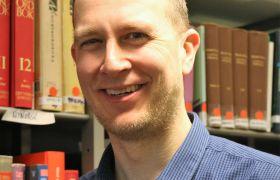 Portrett av filolog Erlend Lønnum. Bokhylle i bakgrunnen. Foto.