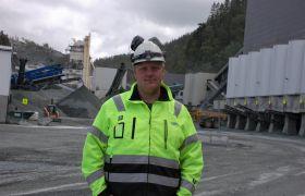 Alf Holte i arbeidsklær med hjelm og øreklokker foran store anleggsmaskiner i dagbruddet der han jobber.