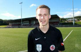 Martin Berg med fotballbane i bakgrunnen.