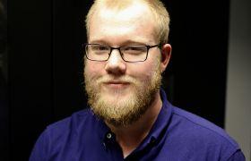 Portrettfoto av IKT-medarbeidar Sebastian Meberg, avbilda frå livet og opp, iført blå skjorte.
