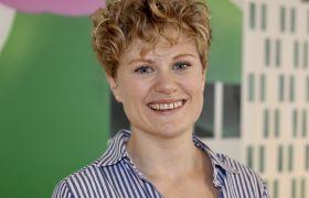 Portrett av Marianne Timby Hartvåg. Ho har på blåstripete skjorte og her lyst, kort, krøllete hår. Fargerik bakgrunn.