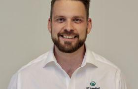 Portrettfoto av kundeansvarleg Magnus Bleie, kledd i kvit skjorte med Stamina-logo.