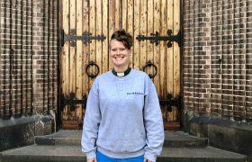 Portrettbilde av diakon Kirsten M. Aase Finch foran kirkedør.