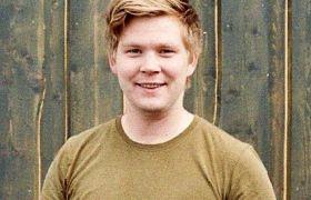 Portrett av tømrer Sigurd Bredal Jenssen i militærgrønn t-skjorte foran et bygg med trekledning.