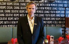Claus Petersen står foran et bord i restauranten på hotellet.
