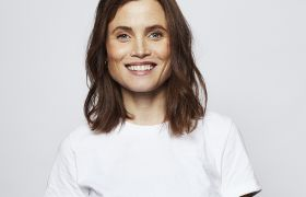 Gitte Witt i hvit t-skjorte mot grå bakgrunn.