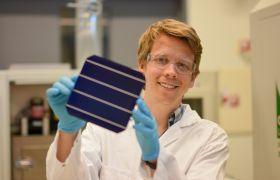 Mann i hvit frakk viser frem et solcellepanel