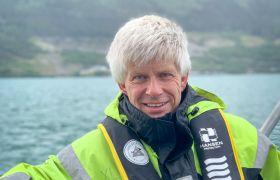 Bildet viser oseanograf Lars Asplin ute i en åpen båt. Han er iført arbeidsdress i neongult og svart, og redningsvest. Han er avbildet fra livet og opp, og vi ser fjorden i bakgrunnen.