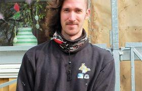 Hjelpearbeider Jonas Rennemo står foran et stillas iført arbeidsklær.